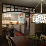 Glass & wood arch divides white kitchen and formal dining room